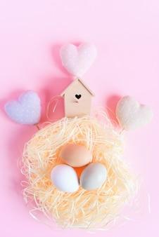 Oeufs de pâques de différentes couleurs dans un nid de paille, mangeoire à oiseaux en bois et coeurs textiles décoratifs sur une surface rose, vue de dessus, mise à plat. concept de pâques.