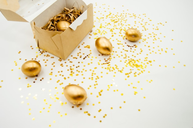 Oeufs de pâques dorés dans une boîte avec des étoiles dorées sur fond blanc