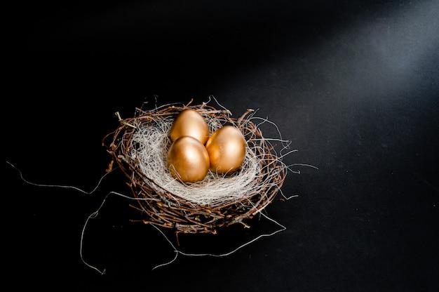 Oeufs de pâques dorés dans un nid d'oiseau sur fond noir