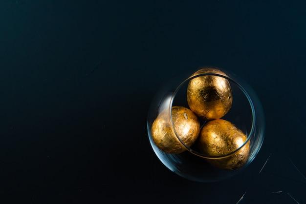 Oeufs de pâques dorés dans un vase transparent sur un fond de béton de couleur bleu classique