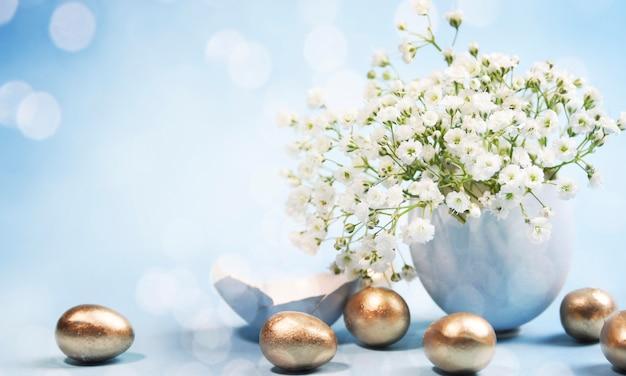 Oeufs de pâques dorés et fleurs avec lumières bokeh