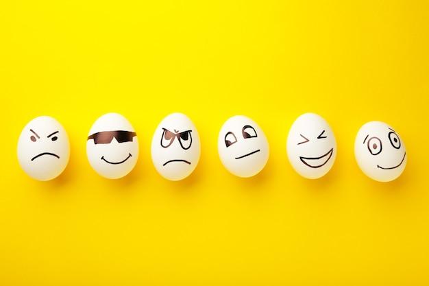 Oeufs de pâques drôles avec différentes émotions sur son visage sur fond jaune.