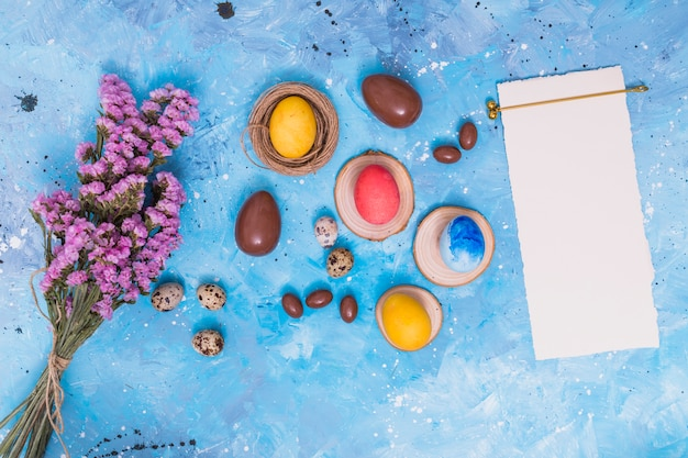 Oeufs de pâques avec du papier et des fleurs sur la table