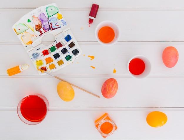 Oeufs de pâques entre les tasses de liquide de teinture près de pinceau avec jeu de couleurs