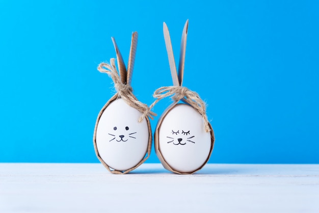 Oeufs de pâques faits maison avec des visages et des oreilles de lapin sur fond bleu. concept de pâques
