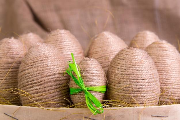Oeufs de pâques en ficelle sur fond en bois marron.