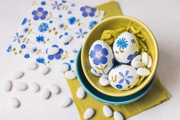 Oeufs de pâques avec des fleurs dans des bols