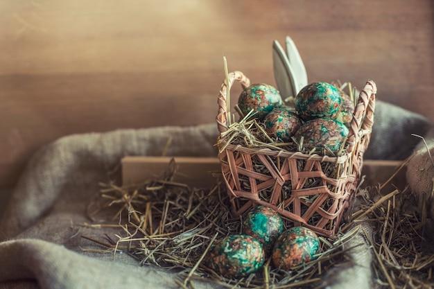 Oeufs de pâques sur fond rustique avec paille, textiles et paniers et oreilles de lapin cachées