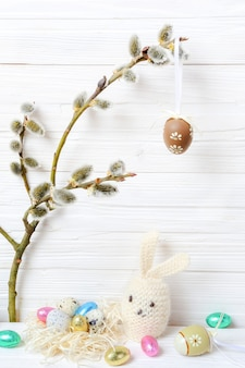 Oeufs de pâques, lapin et chatons sur un fond en bois