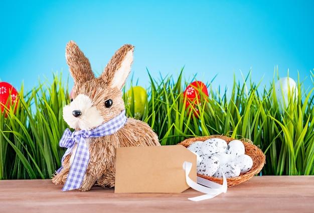 Oeufs de pâques et lapin mignon sur table en bois avec de l'herbe verte. décoration festive