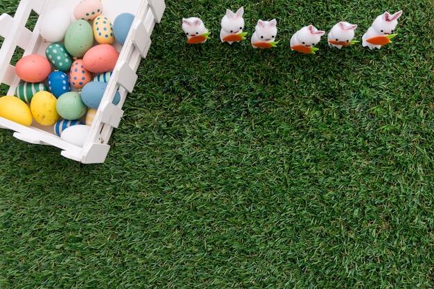 Les oeufs de pâques et les lapins sur la surface de l'herbe