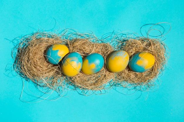 Oeufs de pâques lumineux dans les nids sur la table bleue
