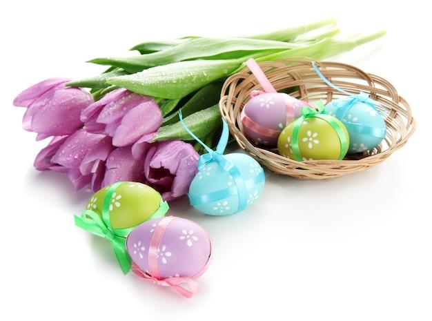 Oeufs de pâques lumineux dans le panier et tulipes, sur blanc