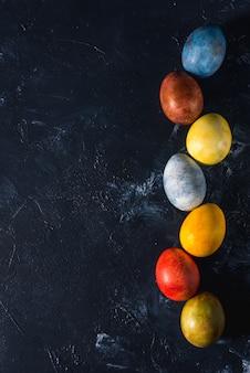 Oeufs de pâques lumineux multicolores. oeufs de pâques sur fond sombre.