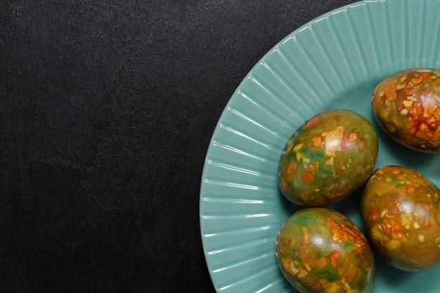 Oeufs de pâques en marbre à la mode moderne de coloration originale sur une plaque bleue sur une ardoise noire