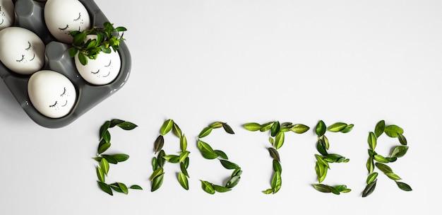 Oeufs de pâques mignons avec un visage peint dans une couronne de printemps avec espace de copie pour le texte. isolé sur fond blanc. joyeuses pâques