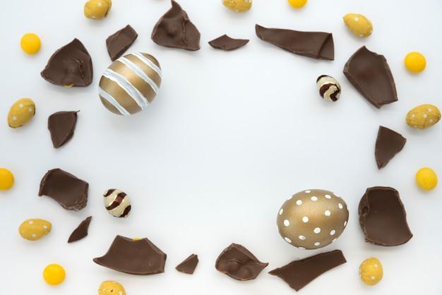 Oeufs de pâques avec des morceaux de chocolat sur une table blanche