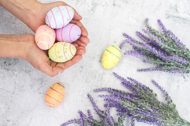 Oeufs de pâques multicolores dans les mains des femmes sur un fond de gros plan de fleurs