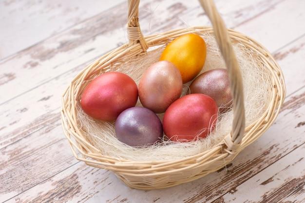 Œufs de pâques. oeufs colorés dans un panier pendant les vacances de pâques. sur fond clair, fond en bois.
