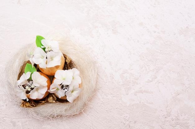 Oeufs de pâques d'or avec des fleurs dans un nid sur une surface texturée