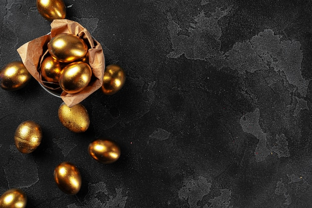 Oeufs de pâques d'or sur fond de béton noir