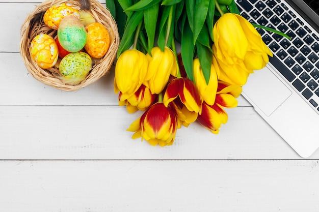 Oeufs de pâques, ordinateur portable et bouquet de tulipes.
