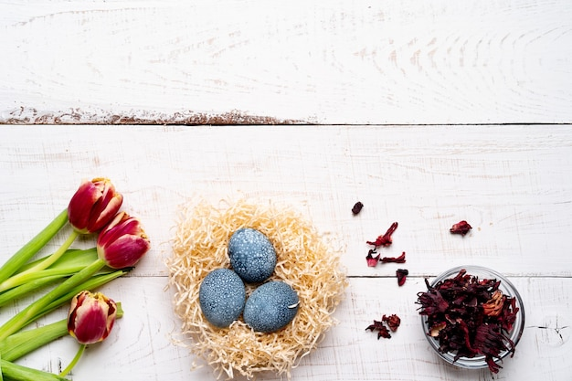 Oeufs de pâques, peints avec des colorants naturels, fleurs d'hibiscus, thé karkade, sur une table en bois vieilli blanc, tulipes de fleurs de printemps rouge.