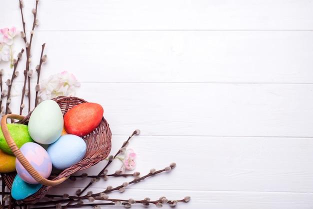 Oeufs de pâques peints colorés dans un panier marron