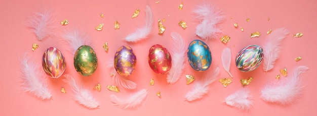 Oeufs de pâques peints colorés avec des plumes blanches et des morceaux de feuille d'or sur le fond rose. bannière de pâques.