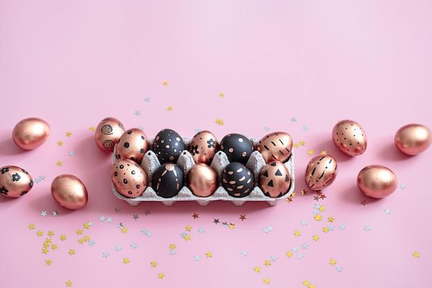 Oeufs de pâques peints de fête sur mur rose.