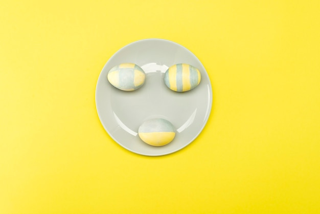 Oeufs de pâques peints en jaune-gris dans une assiette grise sur une surface jaune