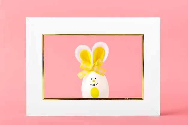 Oeufs de pâques peints lapin mignon avec des visages souriants, des oreilles, un arc et un cadre photo blanc sur fond rose corail.