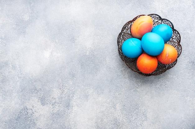 Oeufs de pâques peints à la main colorés sur une table en béton, vue du dessus. copie espace.