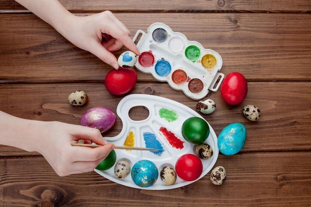 Oeufs de pâques peints à la main, peintures et pinceaux sur fond en bois. préparation pour les vacances. les mains des filles dessinent un motif