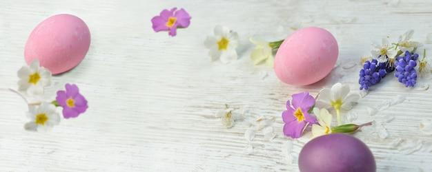 Oeufs de pâques peints en rose et violet sur une table parmi les fleurs et pétales de printemps