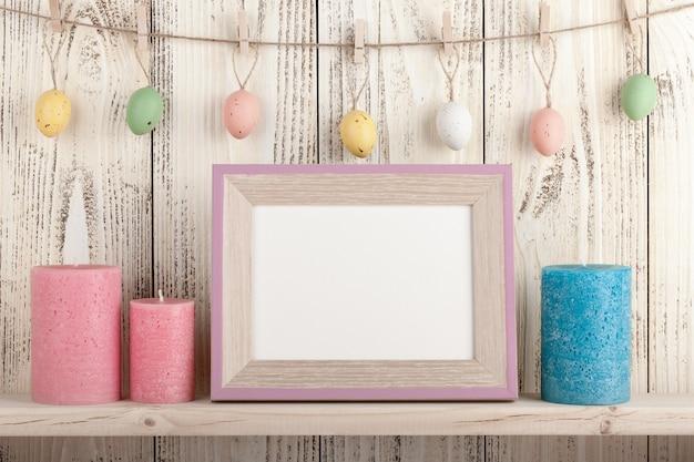 Oeufs de pâques sur des pinces à linge, des bougies et un cadre en bois vierge