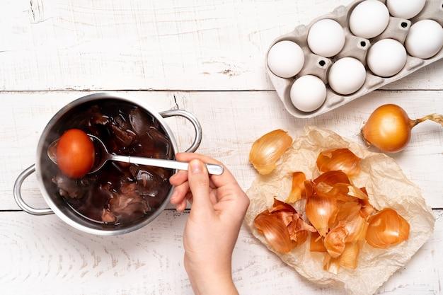 Oeufs de pâques, le processus de coloration avec un colorant naturel, des cosses d'oignon dans une petite casserole sur une table en bois blanc et une main de femme tenant un œuf coloré dans une cuillère.