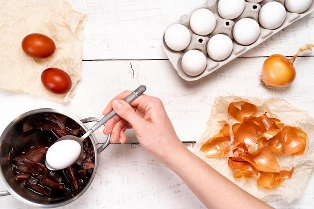 Oeufs de pâques, le processus de coloration avec un colorant naturel, des cosses d'oignon dans une petite casserole sur une table en bois blanc et une main de femme tenant un œuf dans une cuillère.