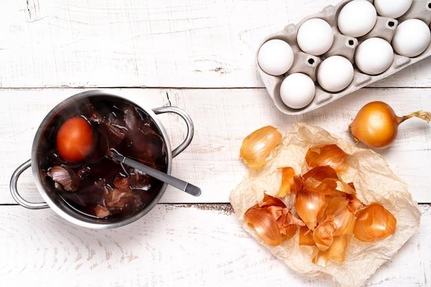 Oeufs de pâques, processus de coloration colorant naturel, cosses d'oignon dans une petite casserole sur une table en bois blanc.