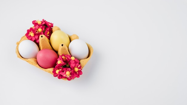 Oeufs de pâques en rack avec des fleurs