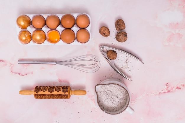 Oeufs de pâques en rack avec des ustensiles de cuisine