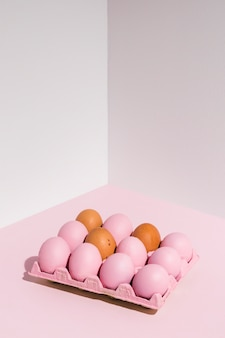 Oeufs de pâques en rose sur une table lumineuse
