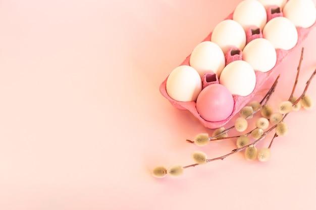 Oeufs de pâques roses et blancs se trouvent sur un substrat à côté d'un saule chatte joyeuses pâques conc