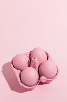 Oeufs de pâques roses dans le support sur la table