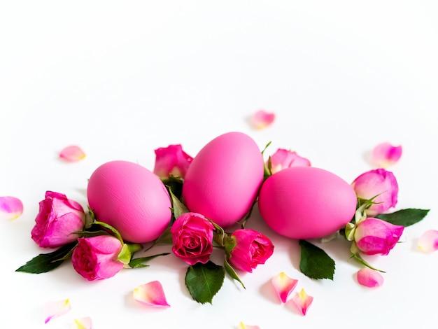 Oeufs de pâques roses sur fond clair avec des roses roses. carte de vacances, espace copie.