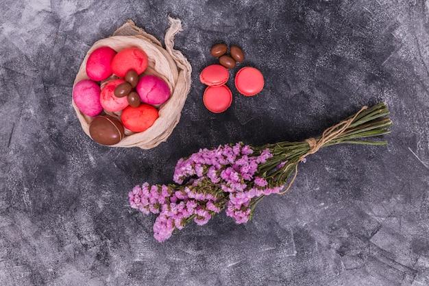 Oeufs de pâques roses avec des macarons et des fleurs