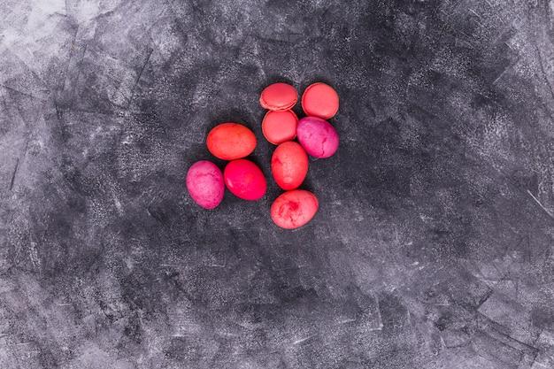 Oeufs de pâques roses avec macarons sur table
