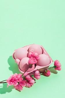 Oeufs de pâques roses en rack avec des fleurs sur la table verte