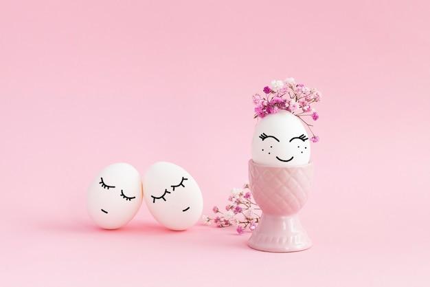 Oeufs de pâques smaly avec des fleurs sur fond rose. oeufs avec des visages souriants. visages dessinés sur les œufs.