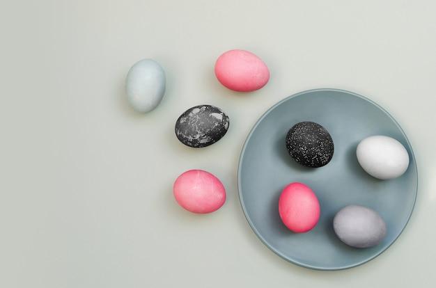 Oeufs de pâques texturés colorés sur plaque bleue et à proximité.